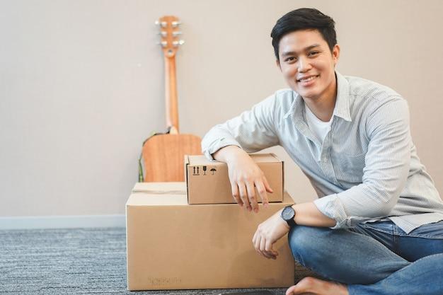 Junger asiatischer mann, der mit kasten und gitarre sitzt, bereiten sich für dekor im neuen wohnsitz vor