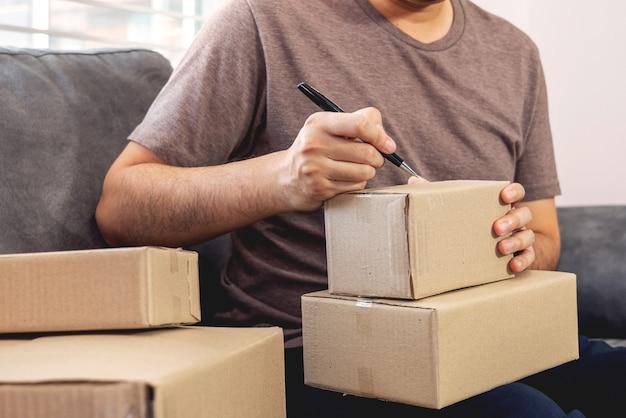 Junger asiatischer mann, der mit laptop-computer und lieferverpackungsbox arbeitet