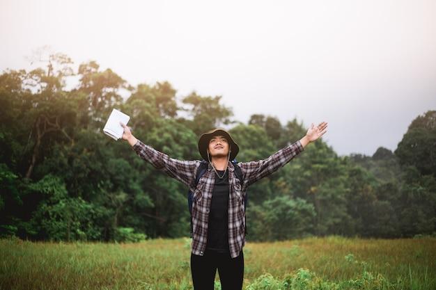 Junger asiatischer mann, der mit seinen armen im wald steht