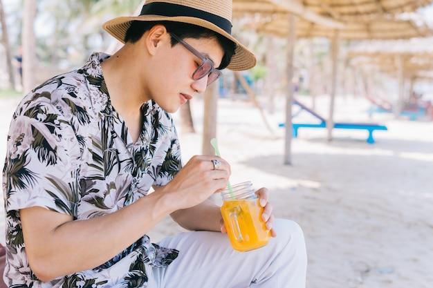 Junger asiatischer mann, der orangensaft am strand trinkt