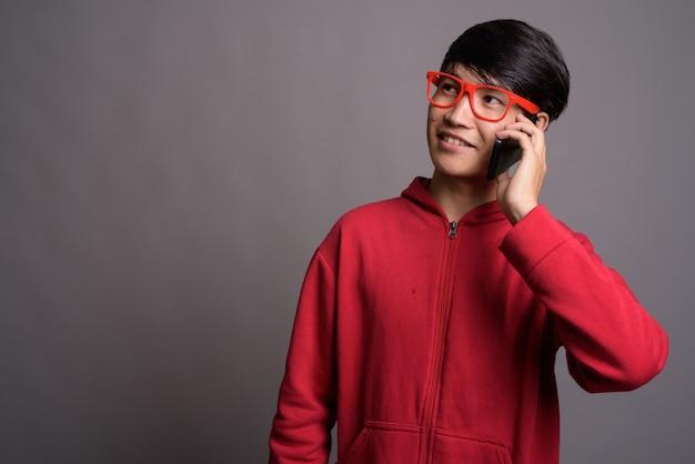 Junger asiatischer mann, der rote jacke mit brille gegen grau trägt