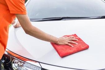 Junger asiatischer Mann, der roten microfiber Stoffreinigungskörper des neuen silbernen Autos verwendet