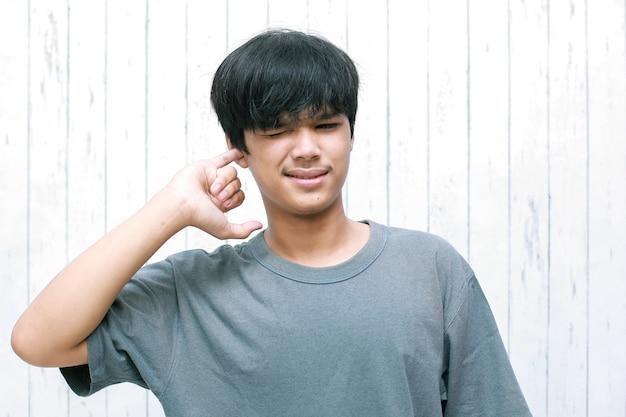 Junger asiatischer mann, der sein ohr mit seinem finger auswählt oder in den ohren juckt