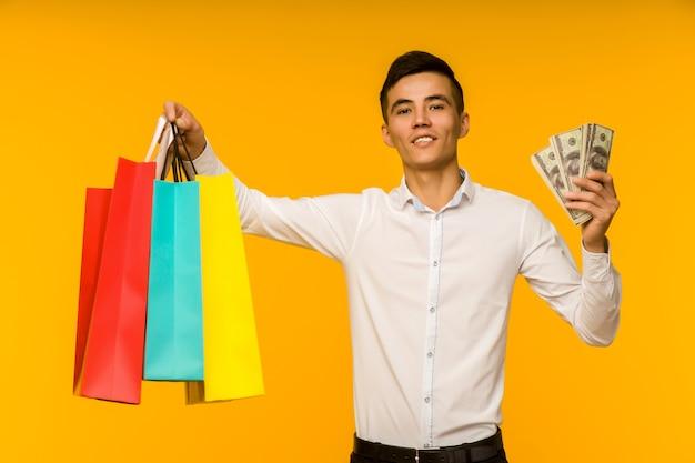 Junger asiatischer mann, der seine einkaufstasche und geld zeigt