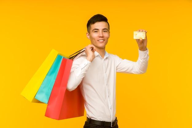 Junger asiatischer mann, der seine einkaufstasche und kreditkarte zeigt