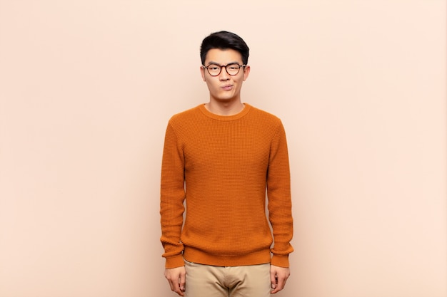 Junger asiatischer mann, der sich verwirrt und zweifelhaft fühlt, sich wundert oder versucht, über farbwand zu wählen oder eine entscheidung zu treffen