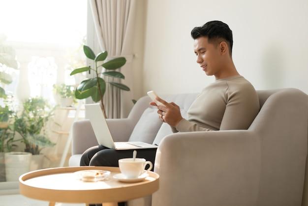 Junger asiatischer mann, der sich zu hause auf einem sofa mit seinem laptop entspannt, der auf seinem handy chattet, während er mit einem lächeln den bildschirm des laptops liest