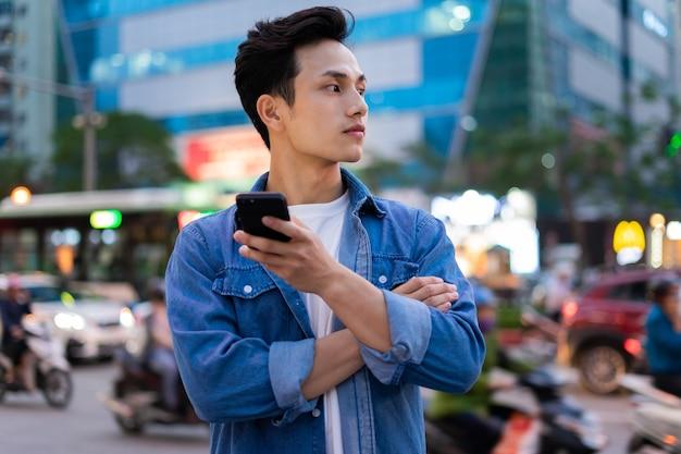 Junger asiatischer mann, der smartphone beim gehen auf der straße in der nacht verwendet