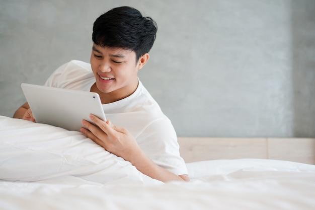 Junger asiatischer mann, der tablette auf bett am wochenende spielt