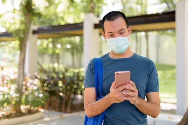 Junger asiatischer mann, der telefon mit maske zum schutz vor coronavirus-ausbruch in der natur im freien verwendet