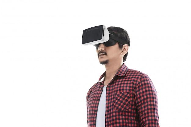 Junger asiatischer mann, der virtuelle realität durch einen vr-kopfhörer erfährt