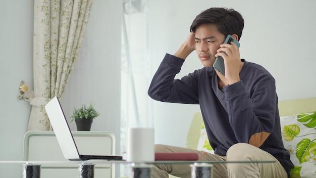 Junger asiatischer mann, der von zu hause aus arbeitet und sich am telefon verwirrt fühlt