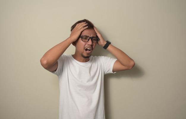Junger asiatischer mann, der weißes t-shirt mit hand auf kopfschmerzen trägt, weil stress unter migräne leidet