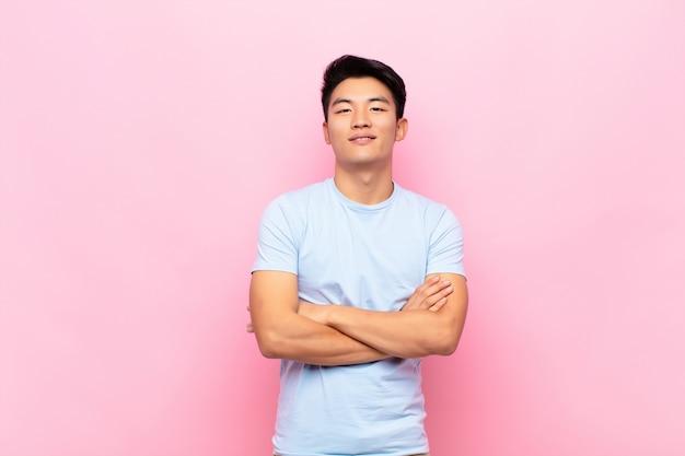 Junger asiatischer mann, der wie ein glücklicher, stolzer und zufriedener leistungsträger aussieht, der mit verschränkten armen über farbwand lächelt