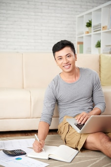 Junger asiatischer mann, der zu hause an dem projekt betrachtet das kamera-lächeln arbeitet