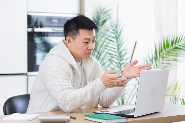 Junger asiatischer mann, der zu hause im wohnzimmer oder in der küche sitzt und online kommuniziert