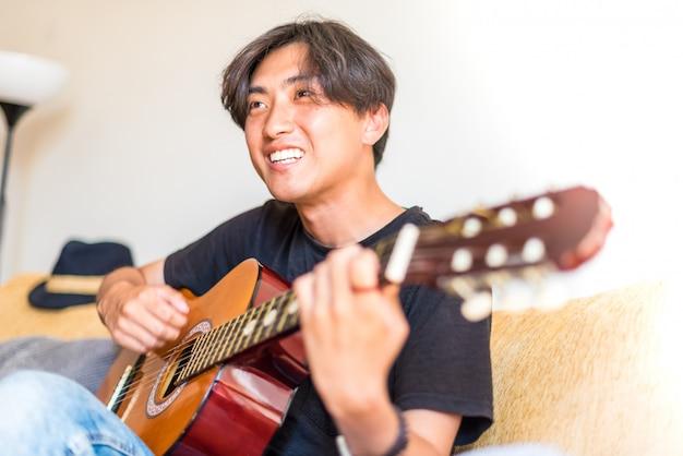 Junger asiatischer mann, der zuhause spanische gitarre spielt