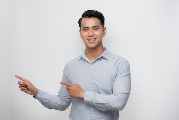 Junger asiatischer mann fröhlich mit einem lächeln des gesichts, das mit hand und finger zur seite mit glücklichem und natürlichem ausdruck zeigt