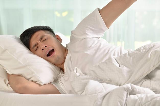 Junger asiatischer mann gähnt und streckt sich beim aufwachen am morgen