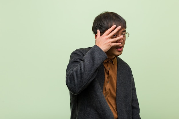 Junger asiatischer mann gegen eine grüne wand