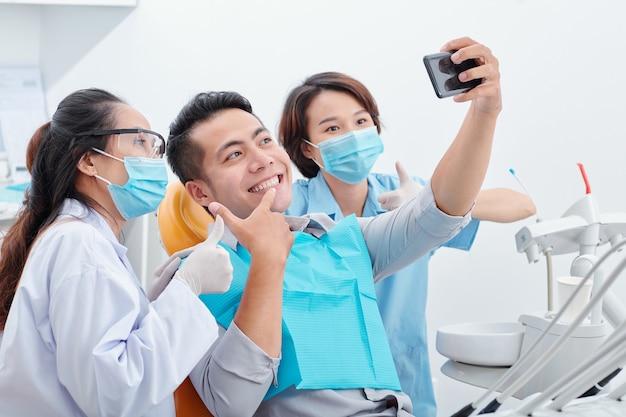 Junger asiatischer mann glücklich mit seinem neuen lächeln, der selfie mit zahnarzt und ihrem assistenten für soziale medien macht