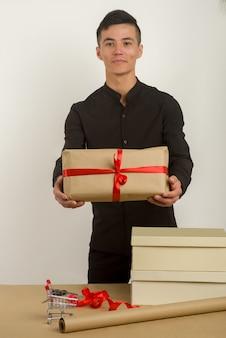 Junger asiatischer mann hält ein geschenkpaket in den händen