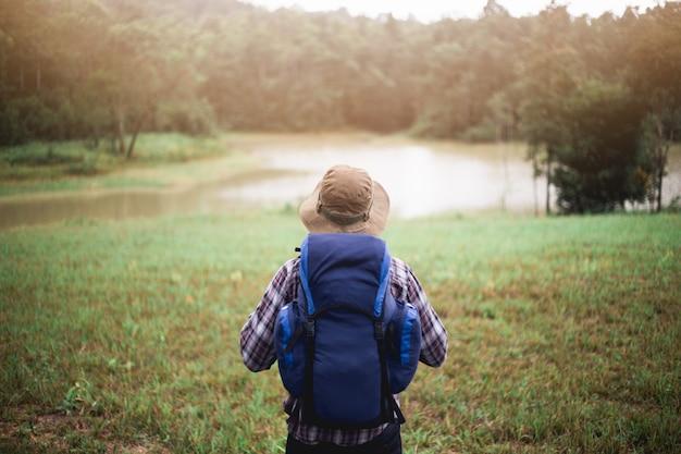 Junger asiatischer mann hat einen rucksack, einen hut und eine karte