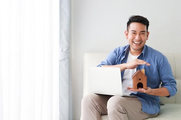 Junger asiatischer mann im blauen hemd mit laptop-computer und modell des kleinen hauses, das für bankdarlehen für hauskonzept im wohnzimmer darstellt