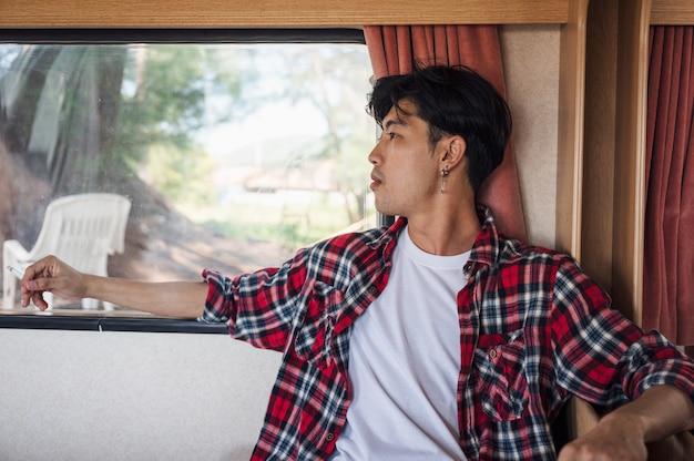 Junger asiatischer mann im scotthemd, der mit rauchender zigarette im wohnmobil im urlaub entspannt