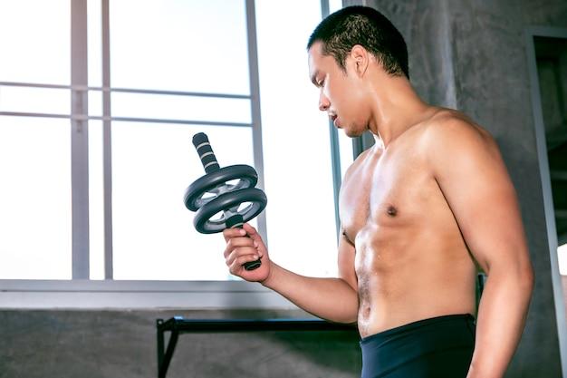 Junger asiatischer mann in der sportkleidung bauchmuskeln mit eignungsrad an der eignungsturnhalle ausbildend.