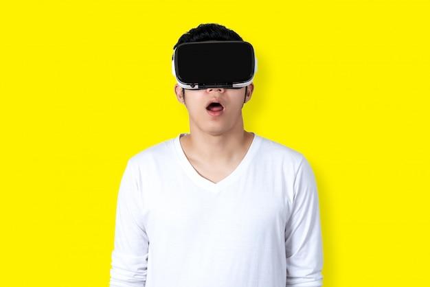 Junger asiatischer mann in der zufälligen weißen ausstattung, die vr-gläser aufpassend video hält oder trägt