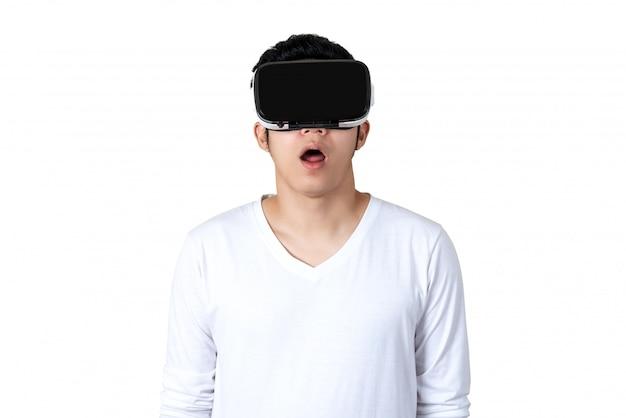 Junger asiatischer mann in der zufälligen weißen ausstattung, die vr-gläser hält oder trägt
