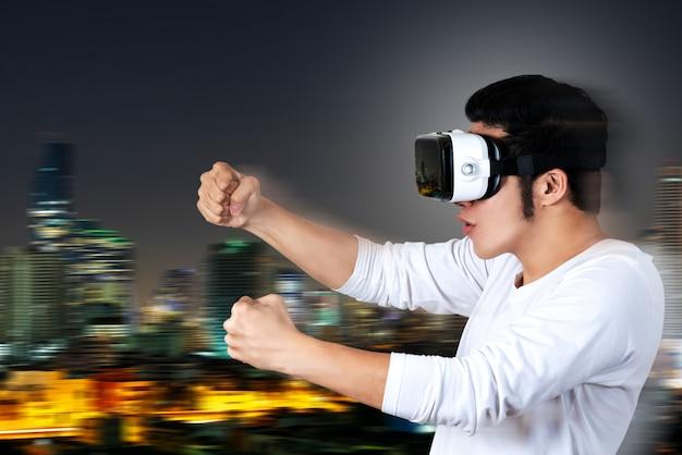 Junger asiatischer mann in der zufälligen weißen ausstattung, die vr-glasbrillen hält oder trägt