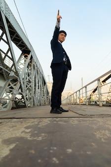 Junger asiatischer mann in einem anzug, der auf einer brücke steht, während oben zeigt