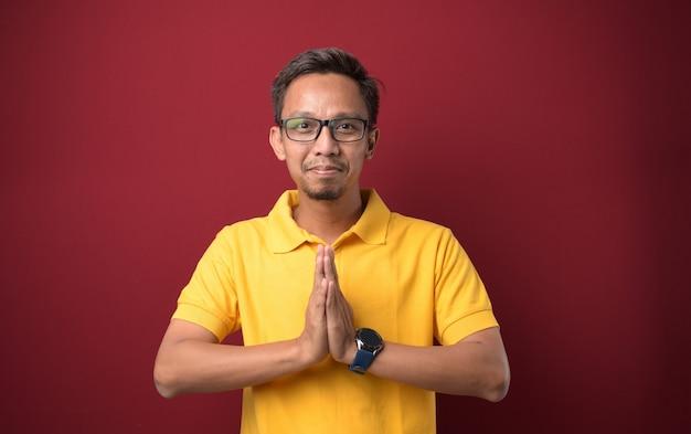 Junger asiatischer mann in freizeitkleidung bettelt und betet mit den händen zusammen mit hoffnungsausdruck