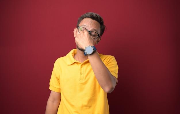 Junger asiatischer mann in freizeitkleidung, der unter kopfschmerzen leidet, verzweifelt und gestresst