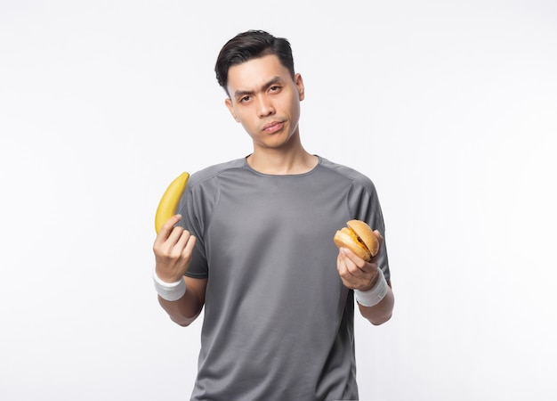 Junger asiatischer mann in sportoutfits, die banane und hamburger mit zweifelsgesicht lokalisieren