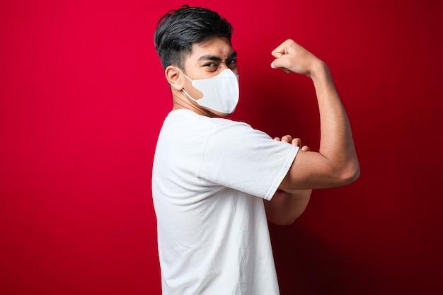 Junger asiatischer mann in weißem t-shirt mit medizinischer maske, der über isoliertem rotem hintergrund steht und die armmuskeln stolz lächelt. fitness-konzept.