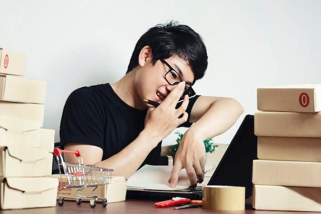 Junger asiatischer mann kleinunternehmer, der zu hause büro arbeitet