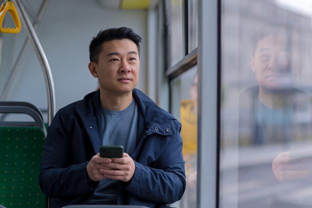 Junger asiatischer mann korrespondiert und liest die nachrichten online, sitzt im bus, ein fahrgast in freizeitkleidung lächelt