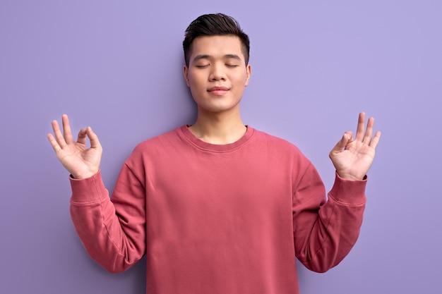 Junger asiatischer mann meditiert, bleibt in yoga-pose mit geschlossenen augen ruhig, chinesischer typ in freizeitkleidung posiert vor der kamera und genießt die zeit allein in der stille.
