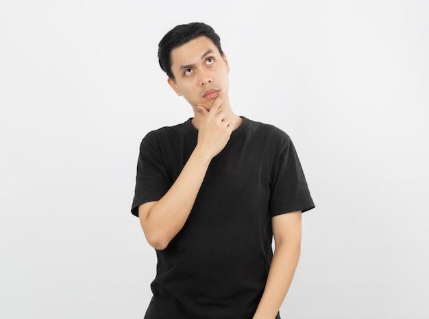Junger asiatischer mann mit dem schwarzen hemd, das zweifel hat und mit verwirren gesichtsausdruck beim verkratzen des kopfes an lokalisiert auf weißer wand.