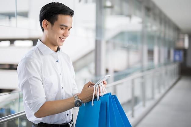 Junger asiatischer mann mit einkaufstaschen benutzt einen handy und lächelt beim handeln des einkaufens