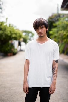 Junger asiatischer mann mit handtätowierungen in den straßen draußen