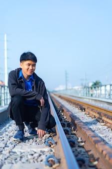 Junger asiatischer mann mit lässiger kleidung kauerte auf einer eisenbahn in ho-chi-minh-stadt, vietnam