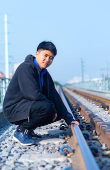 Junger asiatischer mann mit lässiger kleidung mit hand auf eisenbahn in ho-chi-minh-stadt, vietnam
