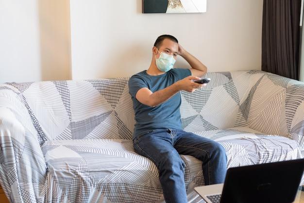 Junger asiatischer mann mit maske, die fernsehen zu hause unter quarantäne sieht
