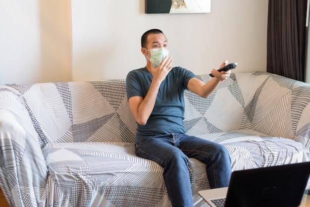 Junger asiatischer mann mit maske, die fernsieht und zu hause unter quarantäne schockiert schaut