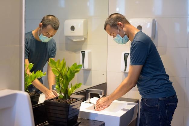 Junger asiatischer mann mit maske, die hände als richtige hygieneetikette im badezimmer wäscht