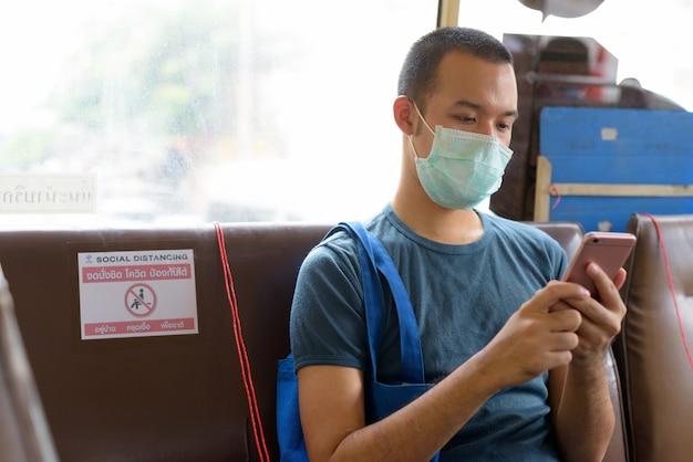 Junger asiatischer mann mit maske unter verwendung des telefons beim sitzen auf dem bus mit entfernung